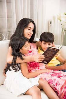 Knappe indiase aziatische vader of mooie moeder die een boek leest voor kinderen terwijl ze thuis op de bank zit