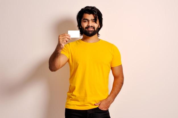Knappe indiase bebaarde jongeman met een stijlvol geel t-shirt met een creditcard die naar came kijkt