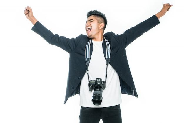 Knappe indiase jonge man met een camera met opgeheven handen op witte achtergrond