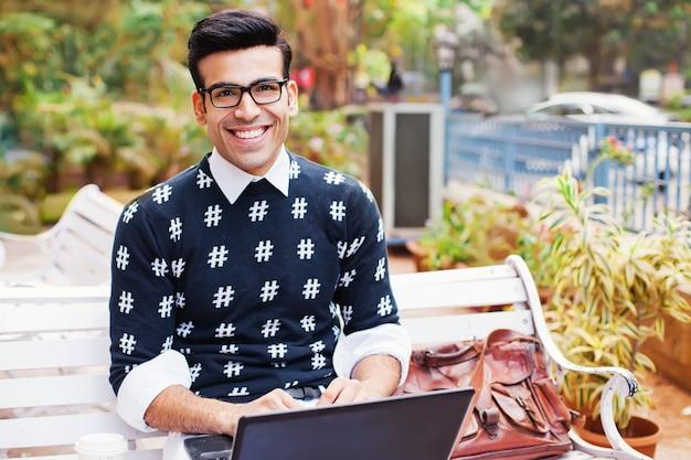 Knappe indiase man aan het werk op zijn laptop
