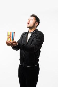 Knappe indiase man met baard die popcorn eet uit grote papieren kan op witte achtergrond