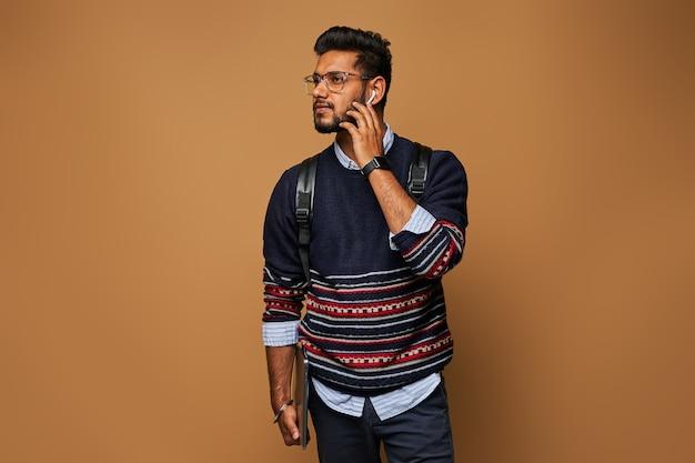 Knappe indiase manager die zijn bluetooth-koptelefoon spreekt, staande met laptop en rugzak.