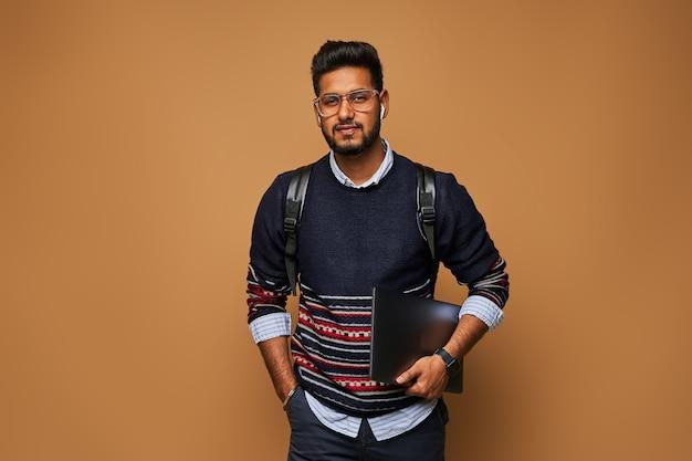 Knappe indiase manager met laptop en rugzak op studiomuur.