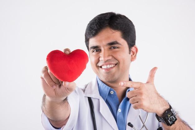 Knappe indiase mannelijke arts die rood gevuld hartspeelgoed vasthoudt als een hartzorgconcept. staande geïsoleerd over blauwe achtergrond
