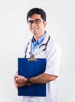 Knappe indiase mannelijke arts met schrijfblok of medische grafiek of rapport, staande geïsoleerd op witte achtergrond
