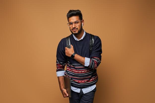 Knappe indiase student in bril en casual close met laptop en rugzak aan de muur.