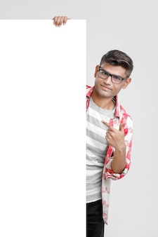 Knappe indische / aziatische mannelijke student die leeg uithangbord toont