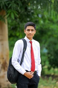 Knappe indische jonge jongen die een wit overhemd en een rode stropdas draagt