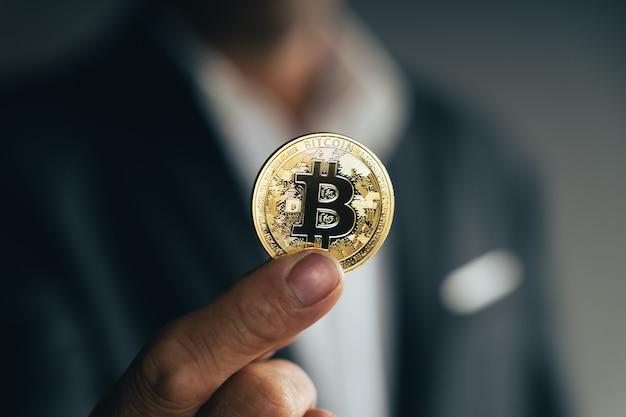 Knappe investeerder zakenman in zwart pak met een gouden bitcoin op donkere achtergrond, handel, cryptocurrency, digitale virtuele valuta, alternatieve financiën en investeringsconcept.