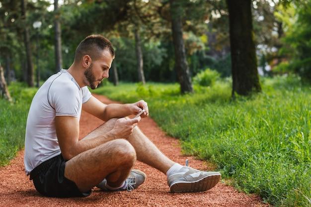 Knappe jogger die internet doorbladeren gebruikend zijn slimme telefoon
