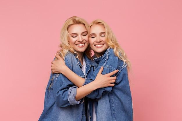Knappe jonge aantrekkelijke langharige blonde dames die de ogen gesloten houden terwijl ze elkaar liefdevol omhelzen, geïsoleerd over roze achtergrond in vrijetijdskleding