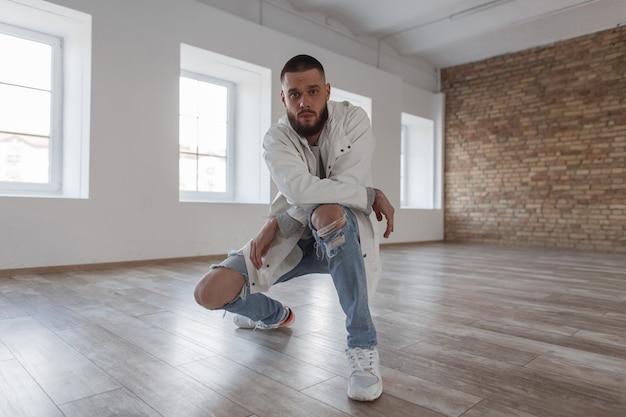 Knappe jonge aantrekkelijke man in mode jas met gescheurde stijlvolle jeans en witte sneakers poseren in studio camera kijken
