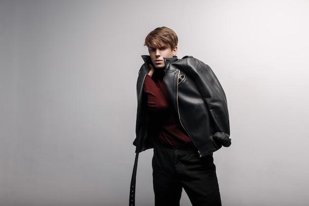 Knappe jonge aantrekkelijke man met een kapsel in een trendy zwart lederen jas in bourgondië stijlvolle golf en stijlvolle zwarte spijkerbroek staat en poseren in een kamer in de buurt van een witte muur. moderne man op stijl