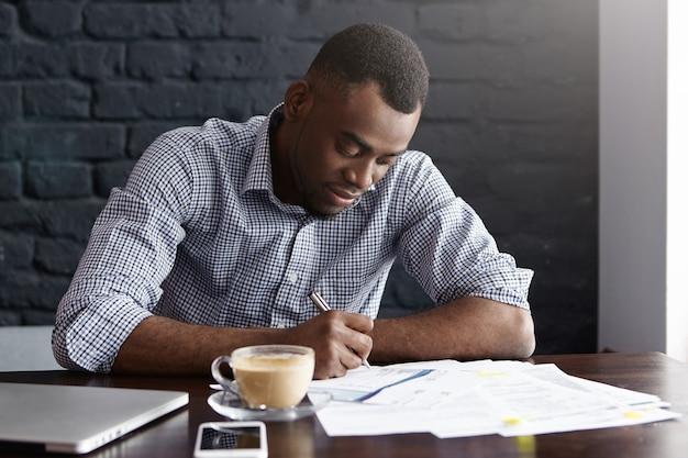 Knappe jonge afrikaans-amerikaanse mannelijke student in overhemd die belangrijke informatie in document ten grondslag liggen
