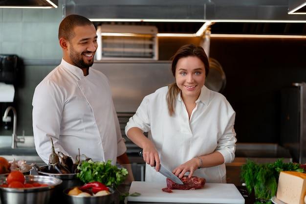 Knappe jonge afrikaanse chef-kok kookt samen met blanke vriendin in de keuken een kok leert een meisje koken. man en vrouw koken in professionele keuken. interraciale relatie