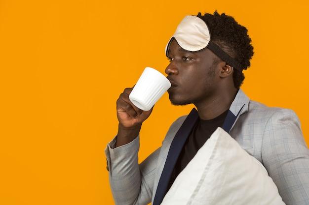 Knappe jonge afrikaanse man in blazer met kussen en mok