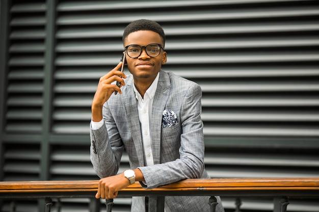 Knappe jonge afrikaanse man in een pak en bril roept op de telefoon