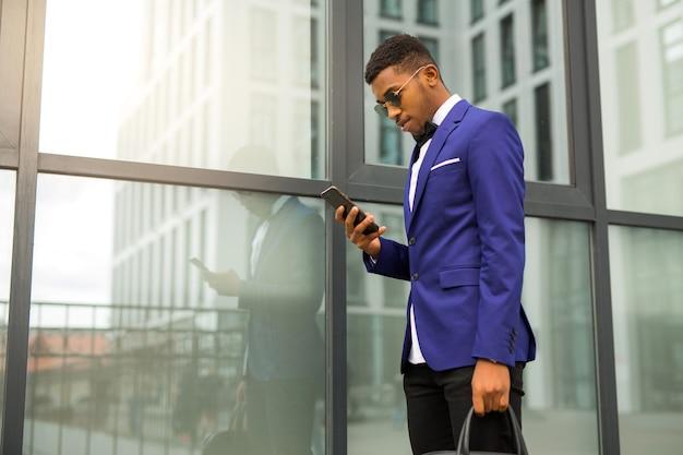 Knappe jonge afrikaanse man in een pak met een telefoon in zijn handen in de buurt van een glazen gebouw