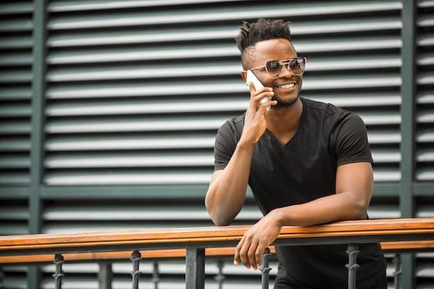 Knappe jonge afrikaanse man in een t-shirt en bril bellen