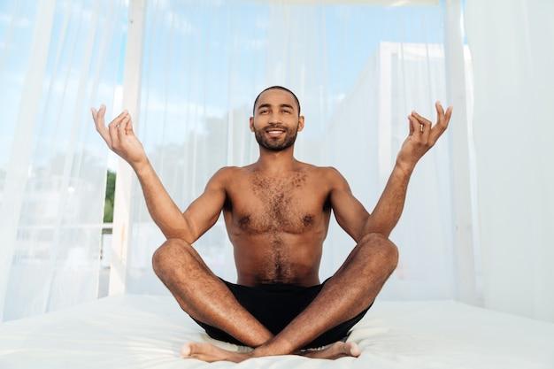 Knappe jonge afrikaanse man in korte broek zitten en mediteren op het strandbed