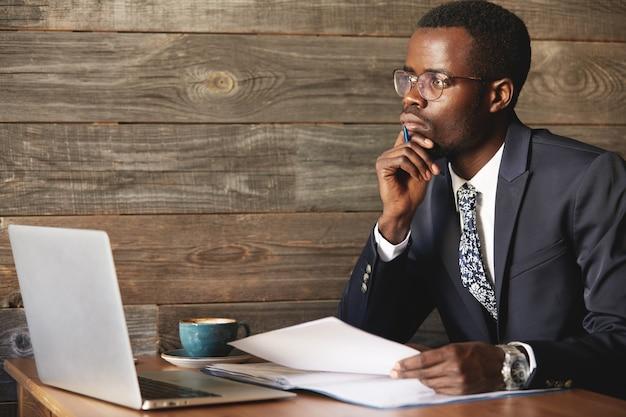 Knappe jonge afrikaanse man met formeel pak zit in een koffieshop