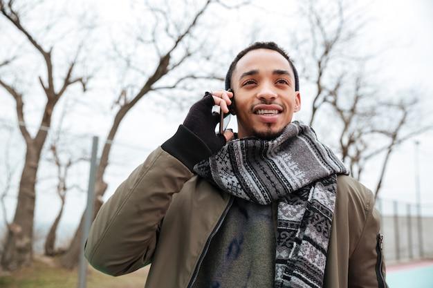 Knappe jonge afrikaanse man praten via de telefoon.