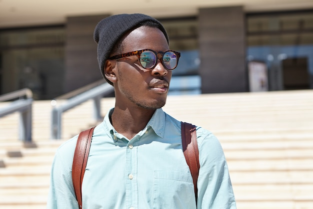 Knappe jonge afrikaanse mannelijke toerist die rugzak draagt die straten van onbekende buitenlandse stad verkent terwijl hij op vakantie in het buitenland, modern gebouw en betonnen trappen