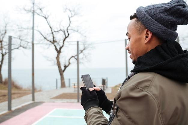 Knappe jonge afrikaanse mens die telefonisch babbelt.