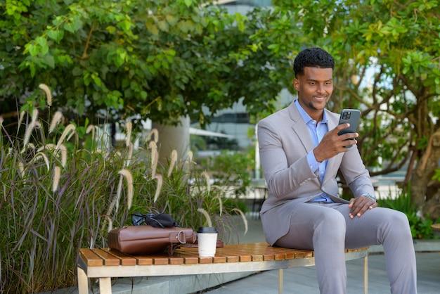 Knappe jonge afrikaanse zakenman die buiten zit terwijl hij een mobiele telefoon gebruikt en glimlacht