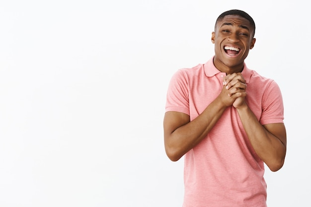 Knappe jonge afro-amerikaan met roze polot-shirt