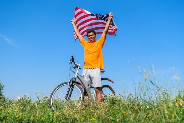 Knappe jonge afro-amerikaanse man die de vlag van de vs vasthoudt en zwaait en met de fiets staat op de zomerweide tegen de blauwe hemelachtergrond in de ochtend