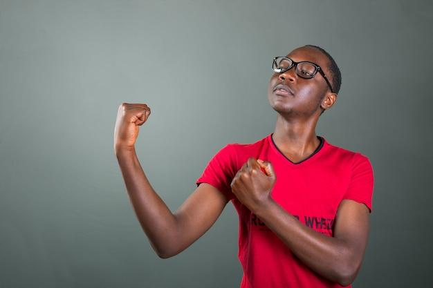 Knappe jonge afro-amerikaanse man, pronken met zijn lichaamsbouw in een agressieve houding
