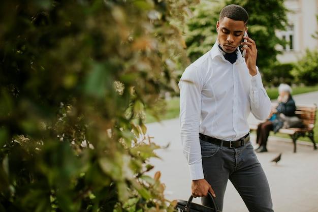 Knappe jonge afro-amerikaanse zakenman die een mobiele telefoon op straat gebruikt