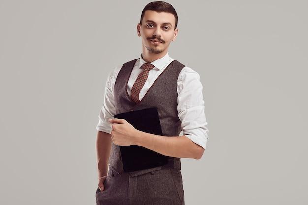 Knappe jonge arabische zakenman met snor in wollen bruin pak