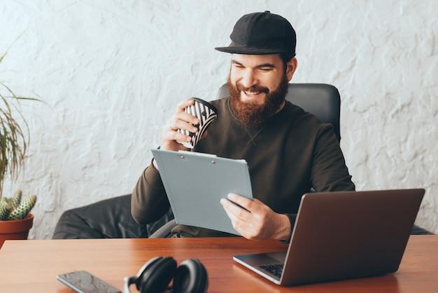 Knappe jonge arbeidersmens in bureau die koffie drinken en documenten lezen