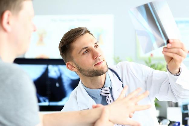 Knappe jonge arts die röntgenstraalbeeld in kliniek controleert