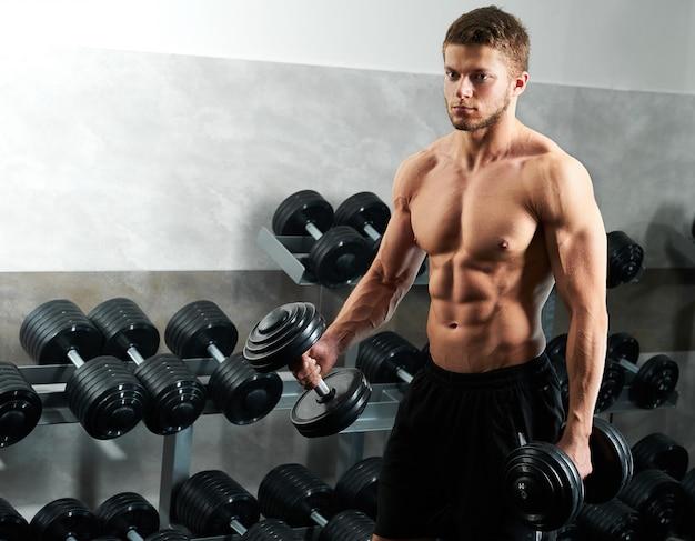 Knappe jonge atleet trainen in de sportschool