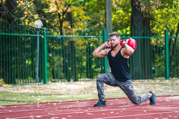 Knappe jonge atleet uit te werken op een atletiekbaan