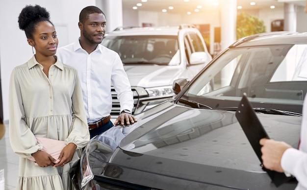 Knappe jonge autoverkoper vertelt over de kenmerken van de auto aan afrikaanse echtpaar