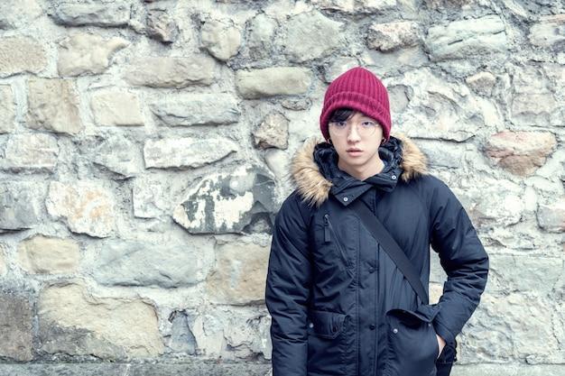 Knappe jonge aziatische kerel in een sweaterjasje dichtbij een oude rotsmuur.