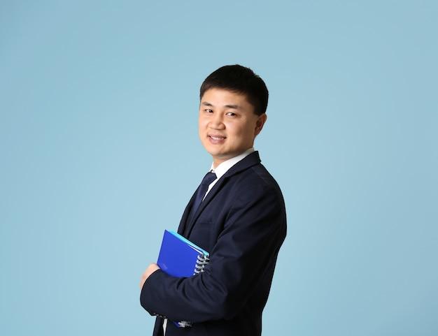 Knappe jonge aziatische leraar op lichte achtergrond