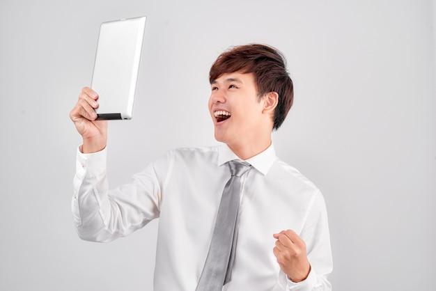 Knappe jonge aziatische man die digitale tablet vasthoudt en ernaar kijkt met een glimlach terwijl hij tegen een witte achtergrond staat