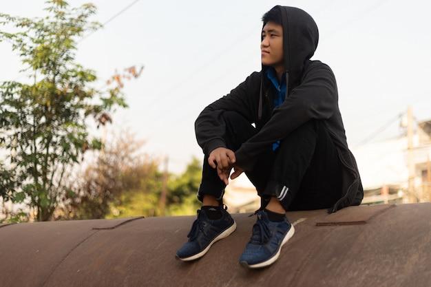 Knappe jonge aziatische man met capuchon zittend op een betonnen pijp en dromerig wegkijken