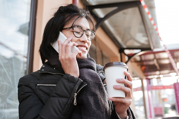 Knappe jonge aziatische man praten aan de telefoon tijdens het drinken van koffie.