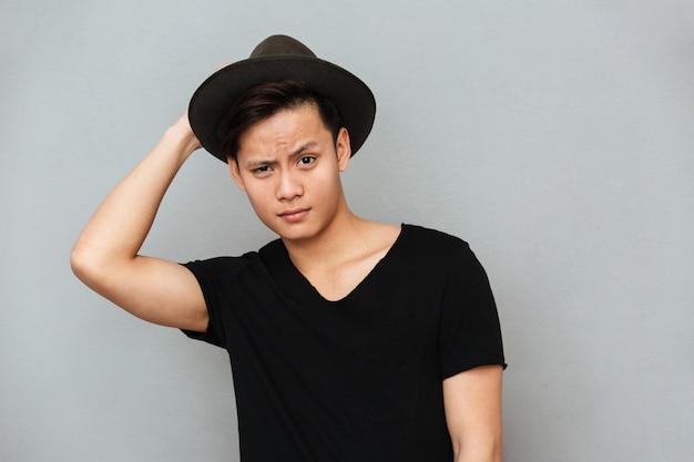 Knappe jonge aziatische mens status geïsoleerd over grijze muur