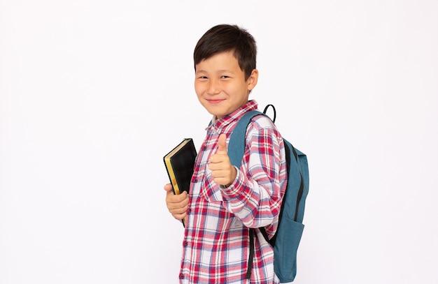 Knappe jonge aziatische schooljongen die met rugzak over witte achtergrond glimlacht