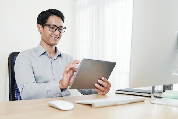 Knappe jonge aziatische softwareontwikkelaarstoepassing die hij voor tabletcomputer heeft gemaakt