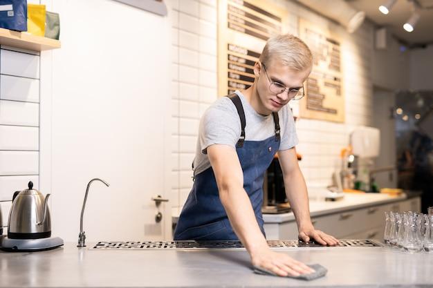 Knappe jonge barista of ober in werkkleding zijn werkplek afvegen met natte stofdoek tijdens de voorbereiding op het werk aan het begin van de dag