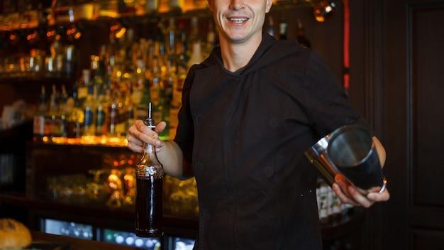 Knappe jonge barman man met een glimlach maakt een cocktail aan de bar