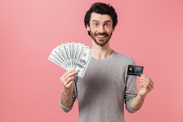 Knappe jonge bebaarde brunette man dragen trui permanent over roze, creditcard tonen, geld bankbiljetten te houden